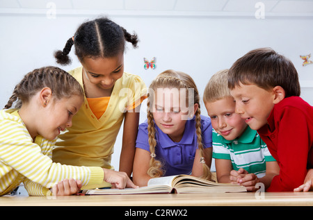 Portrait of pupils looking at page of encyclopaedia at reading lesson - Stock Photo