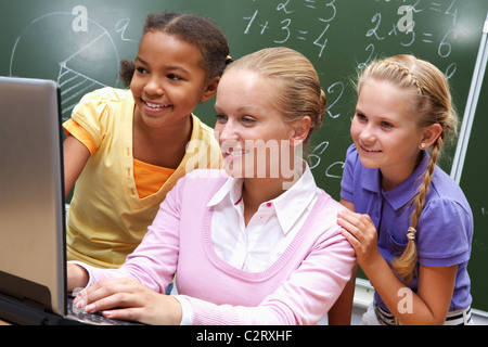 Portrait of two girls and teacher looking at the laptop in classroom - Stock Photo