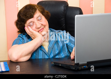 Bored elderly business woman using laptop in office - Stock Photo