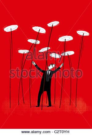 Businessman spinning plates on sticks - Stock Photo