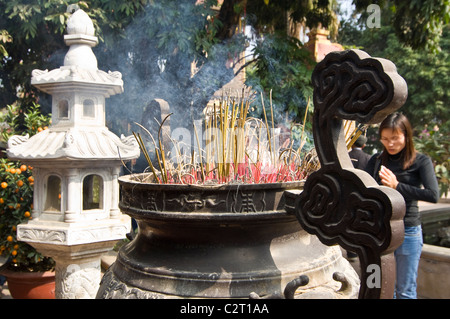 Horizontal close up of a lady praying infront of burning incense in a large censer at Tran Quoc Pagoda (Chùa Trấn - Stock Photo