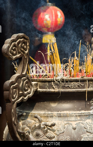 Vertical close up of incense burning in large censer at Tran Quoc Pagoda (Chùa Trấn Quốc) Buddhist temple on West - Stock Photo