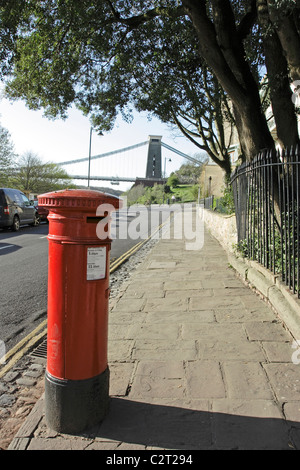 A red post box on Sion Hill in Bristol with the Clifton suspension bridge visible in the background - Stock Photo