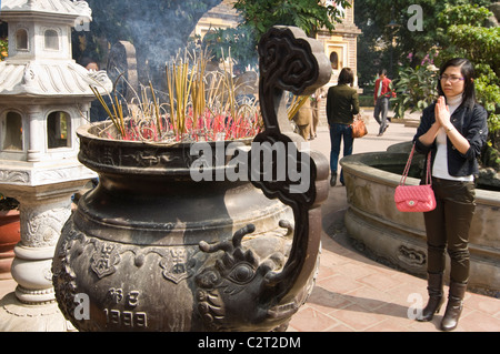 Horizontal close up of incense burning in a large censer at Tran Quoc Pagoda (Chùa Trấn Quốc) Buddhist temple in - Stock Photo