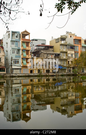 Vertical view of tall thin houses reflected in a lake in a suburban area of central Hanoi. - Stock Photo