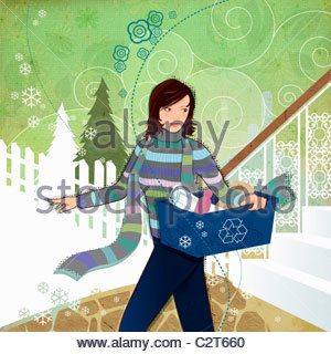 Woman carrying recycling bin in winter - Stock Photo
