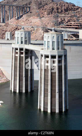 Hoover Dam on Colorado River at Lake Mead. Concrete dam and towers. Tillman memorial bridge in background. Low water - Stock Photo