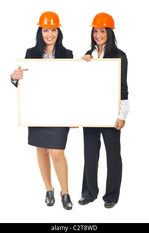 Full length of two architects women holding a blank banner and wearing orange helmets isolated on white background - Stock Photo