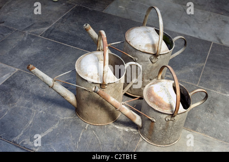Old 1-gallon, 11/2 gallon and 2 gallon galvanised iron watering cans on a slate floor in a greenhouse - Stock Photo