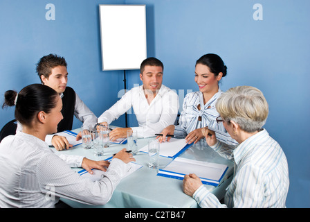 Five business people around a table at meeting laughing together and looking to paperwork of a businesswoman,blank - Stock Photo