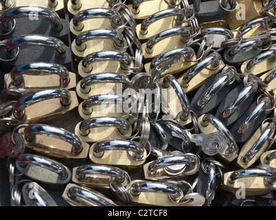 A public market vendor's stall displays the repeated forms of shiny brass and steel padlocks and keys in the city - Stock Photo