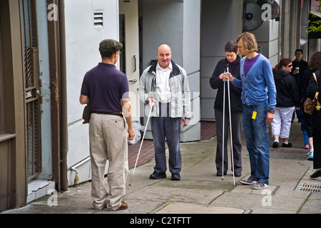 Accompanied by an instructor, a blind man using a white cane teaches two young volunteers how to assist handicapped - Stock Photo