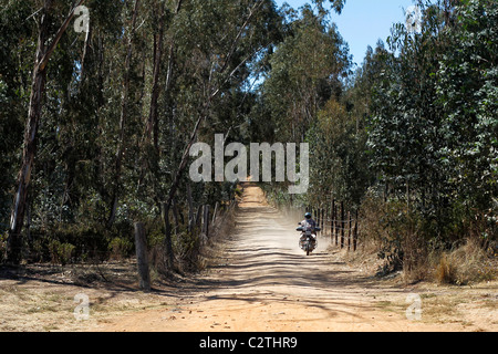 An African man rides a motorcycle down a dusty road in Kenya - Stock Photo