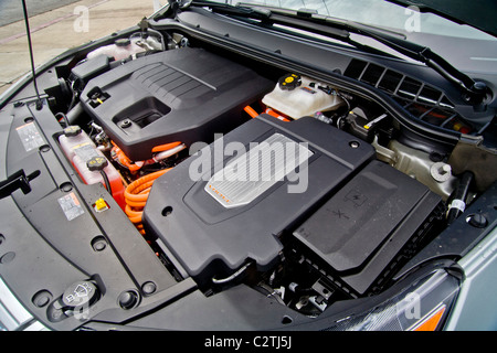 The engine compartment of a Chevrolet Volt hybrid gas/electric car. Right side: the power inverter in top of the - Stock Photo