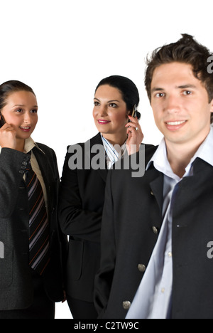 A group of three business people with two happy businesswoman talking on phone mobile in background,focus on them - Stock Photo