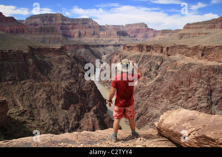 a hiker standing on an overlook in the Grand Canyon looking down into Granite Gorge from the Tonto Plateau - Stock Photo