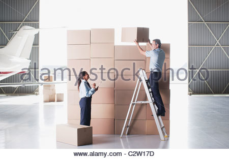 Workers stacking cardboard boxes in hangar - Stock Photo