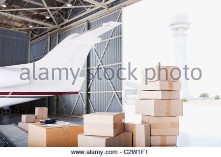 Boxes stacked near airplane in shipping area - Stock Photo