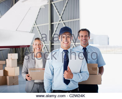 Supervisor and workers standing in hangar - Stock Photo