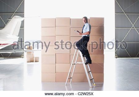 Worker stacking boxes in hangar - Stock Photo