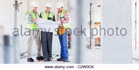 Construction workers looking at blueprints on construction site - Stock Photo