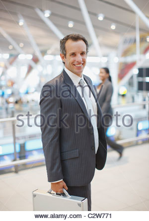 Businessman standing with briefcase in airport - Stock Photo