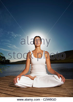 Woman practicing yoga on pier - Stock Photo