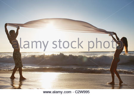 Couple standing on beach and holding fabric - Stock Photo
