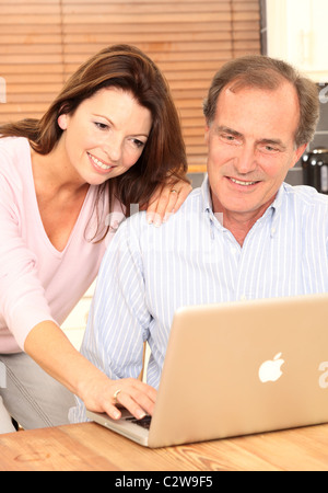 Mature couple using a laptop in the kitchen together - Stock Photo