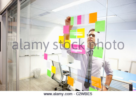 Businessman putting adhesive notes on conference room wall - Stock Photo