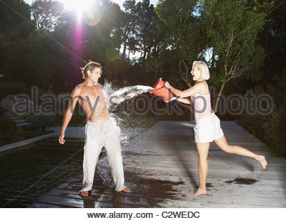 Playful woman throwing bucket of water on boyfriend - Stock Photo