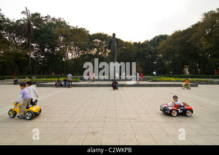 Horizontal wide angle of young children driving around Lenin's statue in battery operated cars in Lenin Park, central - Stock Photo