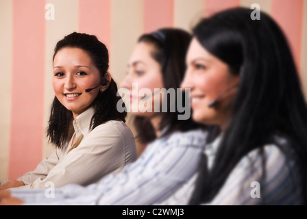 Three women customer service team sitting in line at desktop ,focus on last young woman which looked at you and - Stock Photo