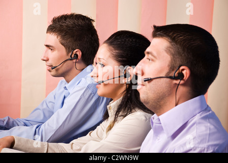Three office workers working in a call center and sitting on chair in profile,looking to screens,woman in middle - Stock Photo