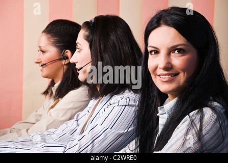 Friendly team of customer service team standing in line,focus on first brunette woman which looked you and smiling - Stock Photo