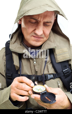 Portrait of mature man looking at compass on trip - Stock Photo