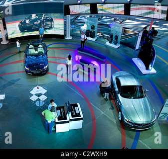 Germany, Bavaria, Munich, BMW World, People in showroom examining new BMW cars. - Stock Photo