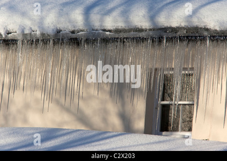 Icicles on house in winter cold snap, UK - Stock Photo