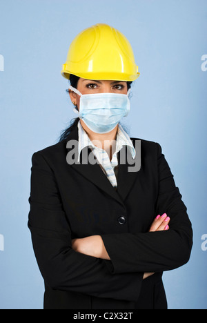 Architect woman with helmet and protective mask standing with hands folded and looking you,concept of protection - Stock Photo
