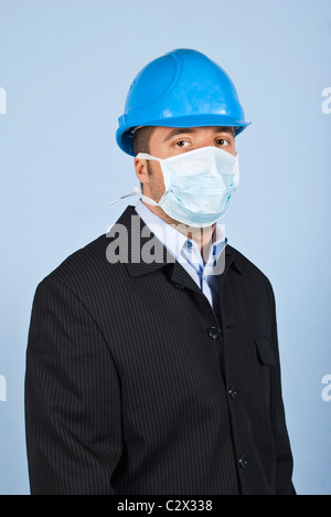 Young architect man standing in profile ,facing you and wearing helmet and protective mask,concept of protection - Stock Photo