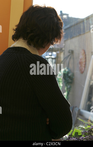 Back view lonely mature woman alone sadness, looking out of window at home. - Stock Photo