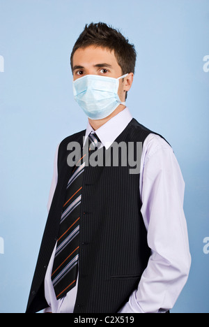 Young business man with protective mask standing on blue background,concept of protection from flu at work - Stock Photo