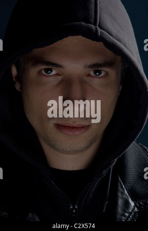 Young man in black hood and jacket in darkness - Stock Photo