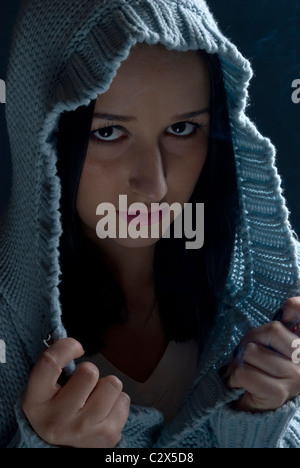 Portrait of girl with evil look wearing wool hood in darkness with smoke around - Stock Photo