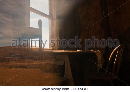 A dining table and chairs in a former residence in California's Bodie State Historic Park, seen through a dusty - Stock Photo