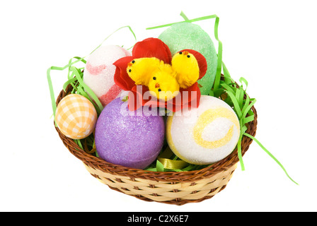 Easter basket with eggs and little chicken in a flower isolated on white background - Stock Photo