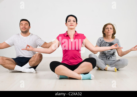 Group of people doing yoga and sitting on floor - Stock Photo