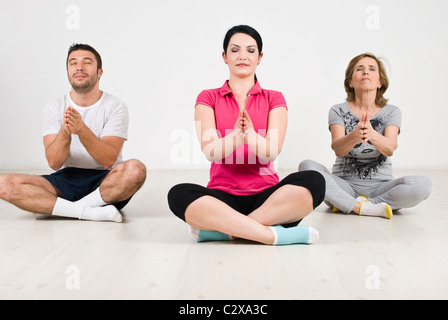 Three members of a family doing yoga on wooden floor in their home - Stock Photo