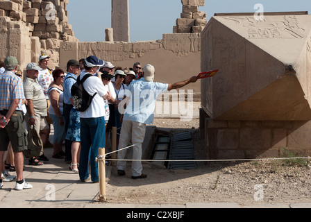 Egyptian guide with tourists near the Fallen Obelisk of Hatshepsut - Temple of Amun - Karnak Temple Complex - Luxor, - Stock Photo