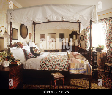 Period style four poster bed with floral pattern bedcover - Stock Photo